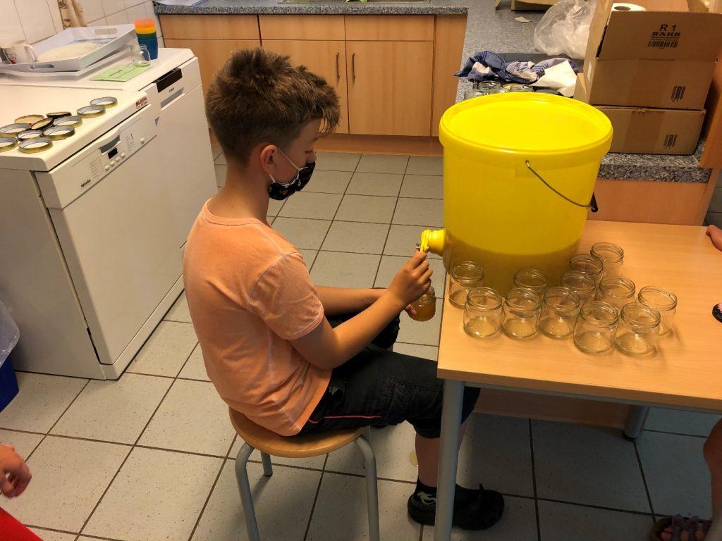 Ein Schüler mit Mund- Nasenschutz füllt sitzend Honig aus einem Hobbock ab